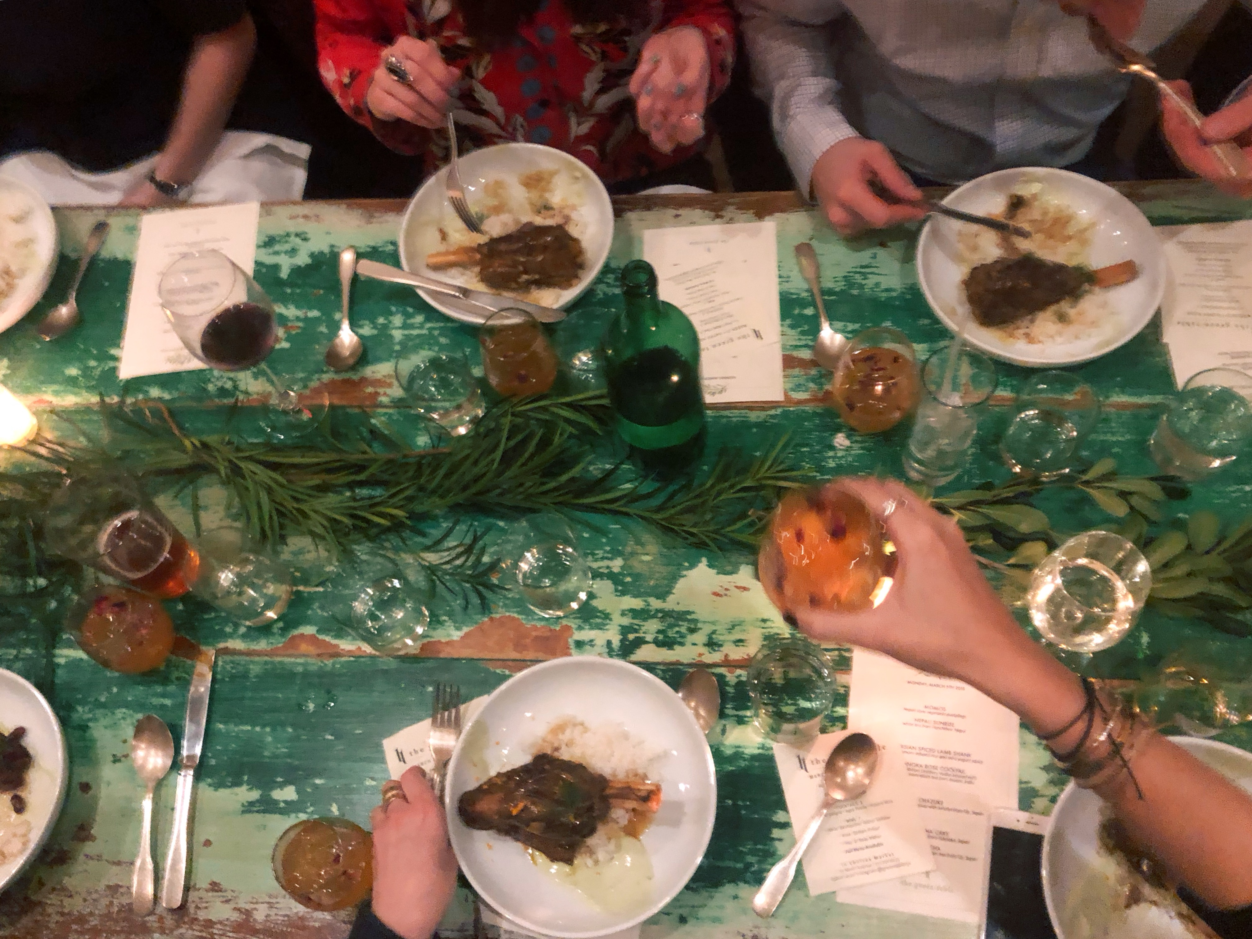 Flatlay photo of rustic green, wooden table with plates of food and diners around it.